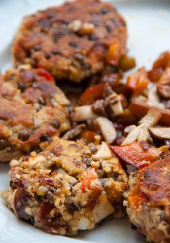 A close-up of lentil burgers with mushrooms and bell pepper