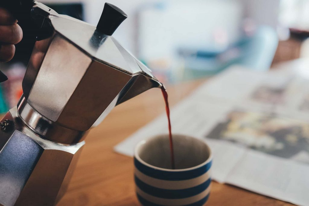 Coffee being poured into a coffee cup out of a moka pot