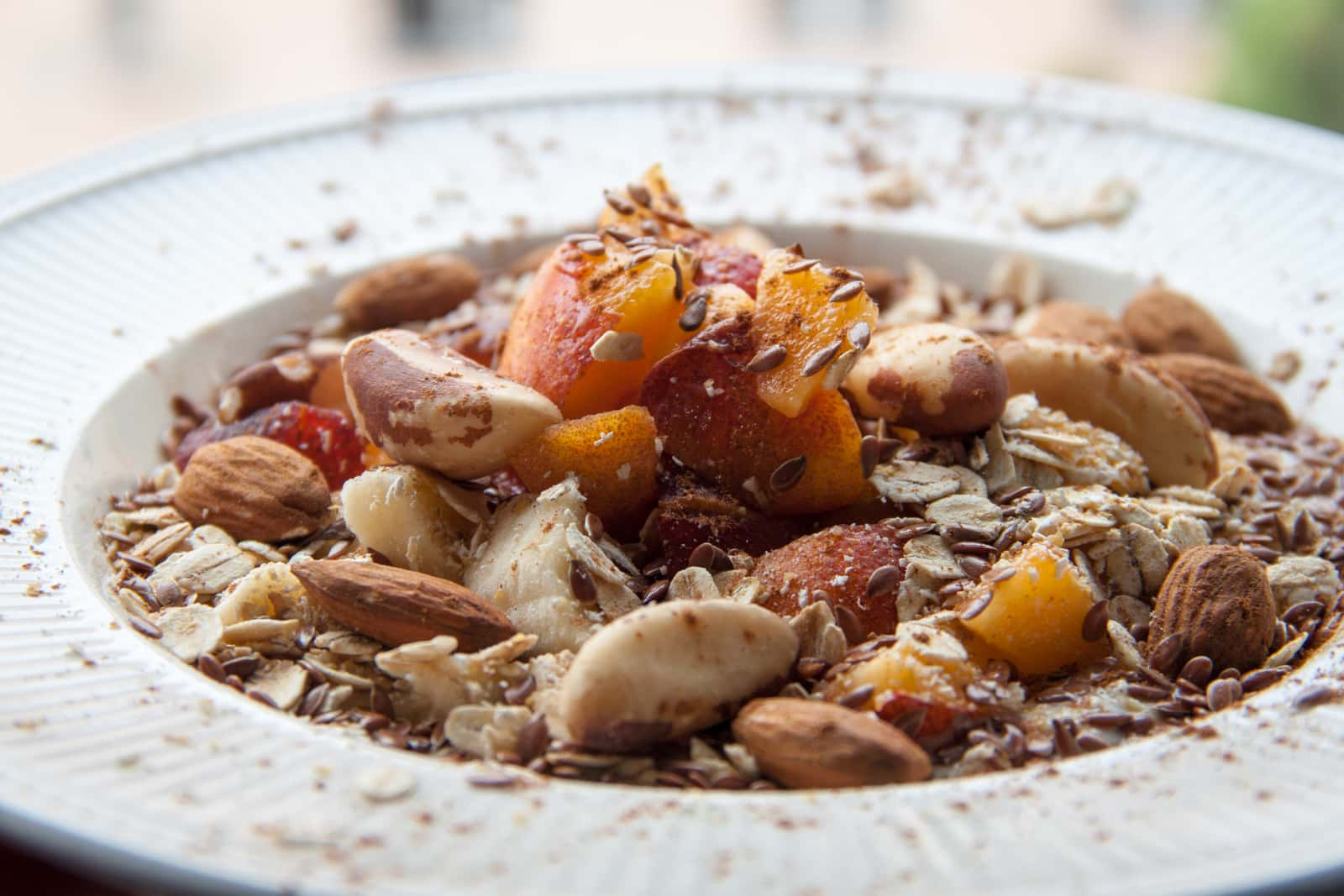 A close up of oats with yoghurt, fruit and nuts