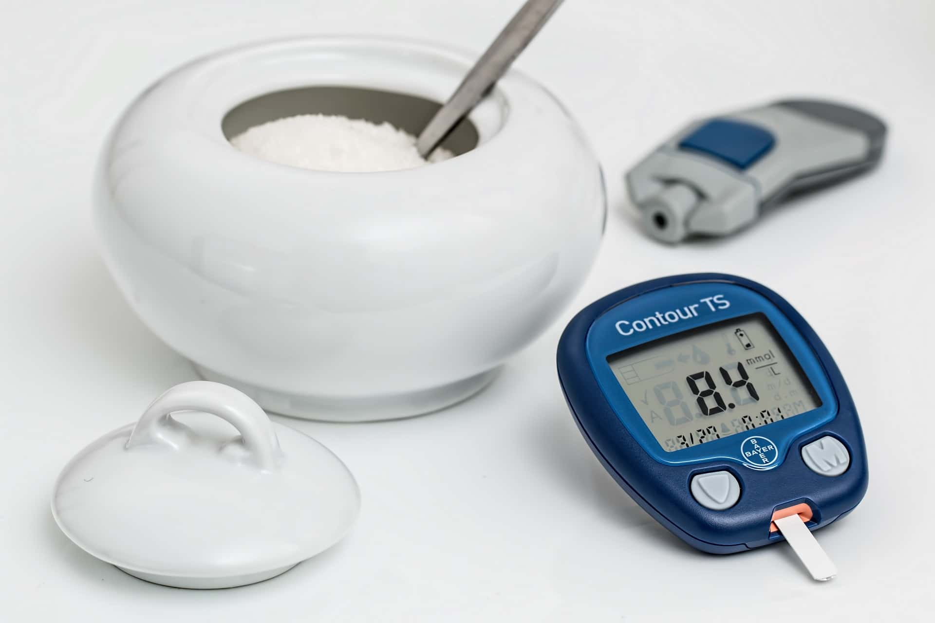 A bowl of sugar with a glucose monitor for diabetics